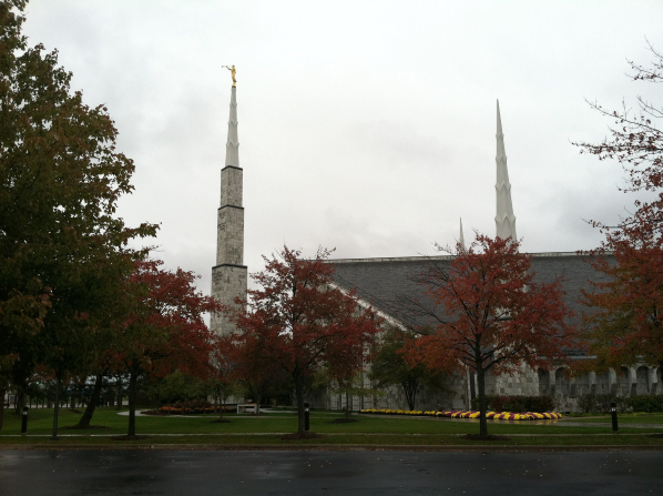 The spires on the Chicago Illinois Temple during the autumn, with red and orange leaves on the trees in the foreground.