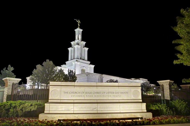 "A sign reading ""The Church of Jesus Christ of Latter-day Saints: Columbia River Washington Temple,"" lit up at night with the temple in the background."