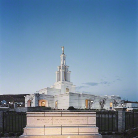The Columbia River Washington Temple in the evening, with the temple's sign in the foreground lit up by lights on the ground.