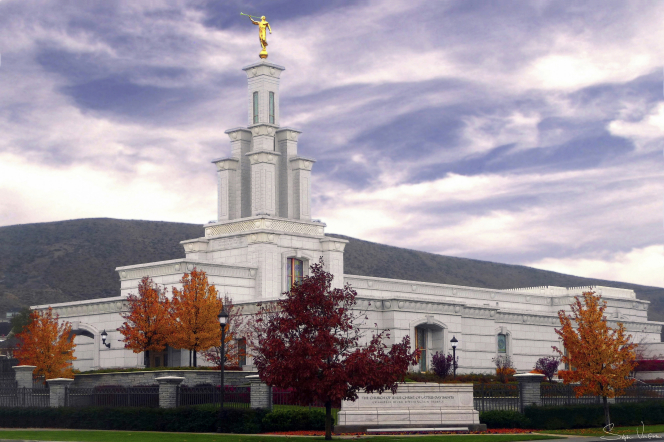The Columbia River Washington Temple exterior on a fall day, with a hill in the background.