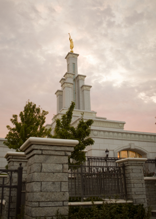 A view from the ground looking up toward the spire of the Columbia River Washington Temple, with the stone pillars of the fence in the foreground.
