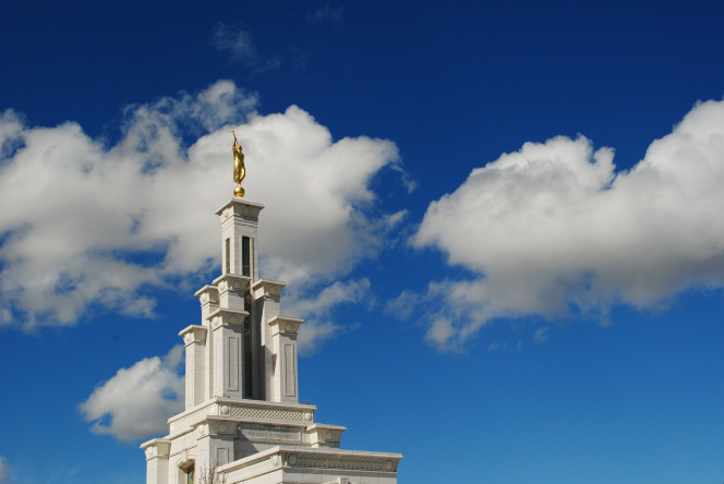 The spire on top of the Columbia River Washington Temple, with a deep blue sky and clouds in the background.