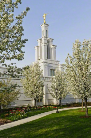 The front of the Columbia River Washington Temple on a spring day, with the trees on the grounds in bloom.