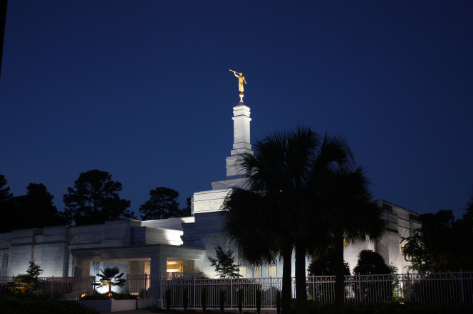Lights shining around the entrance and side view of the Columbia South Carolina Temple at night.