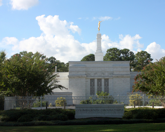 The stone name sign in front of the Columbia South Carolina Temple, surrounded by a green lawn and trees.