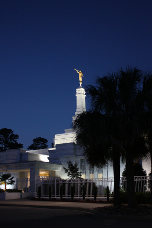 A portrait view of the Columbia South Carolina Temple lit up at night, with a fence and a tree in front.
