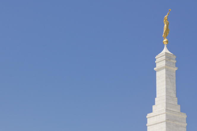 The spire and angel Moroni on top of the Columbia South Carolina Temple, with a blue sky in the background.
