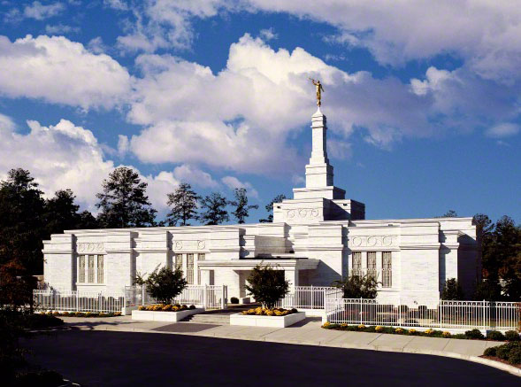 The front of the Columbia South Carolina Temple during the daytime, with a portion of the parking lot in the foreground.