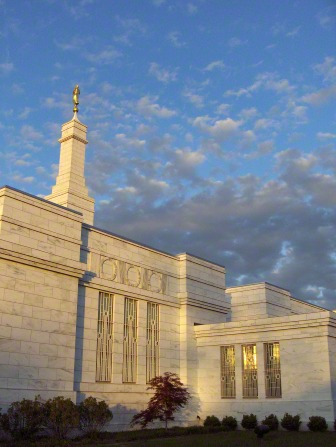 One side of the Columbus Ohio Temple, with the spire and angel Moroni in view and a blue sky with clouds in the background.