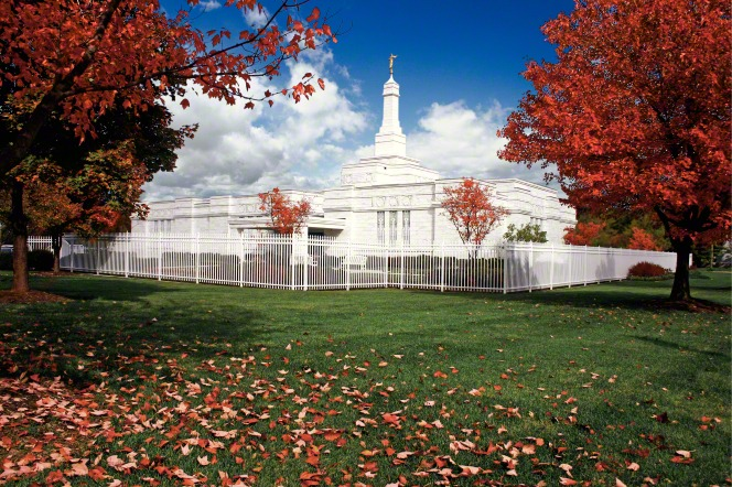 The grounds of the Columbus Ohio Temple on a fall day, with red leaves falling from trees and the temple in the background beyond the fence.