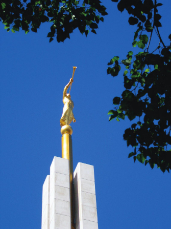 The angel Moroni statue on the spire of the Copenhagen Denmark Temple, framed by green leaves on a nearby tree.