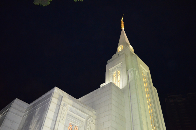 The Curitiba Brazil Temple spire lit up at night against the black sky.