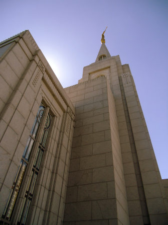 A view of the spire on the Curitiba Brazil Temple, looking up from the ground past a large stained-glass window.