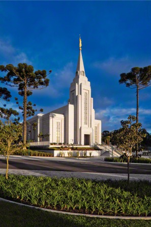 A portrait view of the Curitiba Brazil Temple on a sunny day, with a deep blue sky above and green plants and trees surrounding the building.