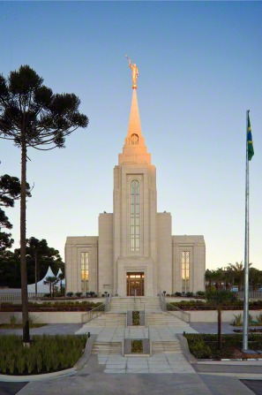 The Curitiba Brazil Temple in the evening, with a set of stairs leading to the front entrance and the Brazilian flag nearby.
