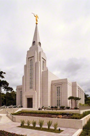 The Curitiba Brazil Temple on an overcast day, with large flower beds lined with green plants in the front.