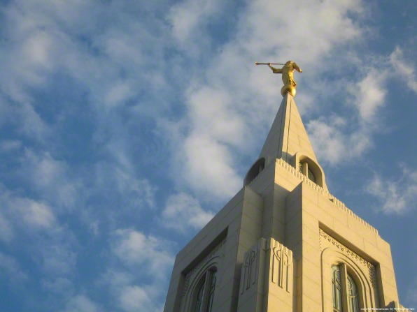 A view from below, looking up toward the spire on the Curitiba Brazil Temple, with a blue sky and white clouds behind.