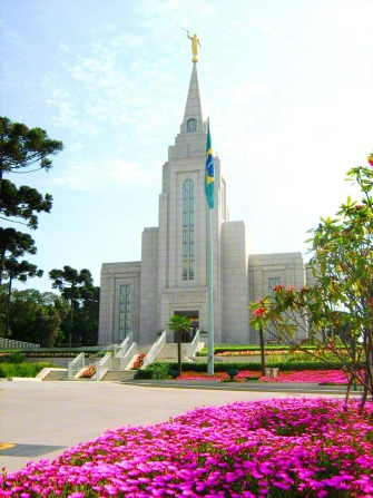 The Curitiba Brazil Temple on a sunny day, with a large flower bed of pink flowers in the foreground and the Brazilian flag near the spire.