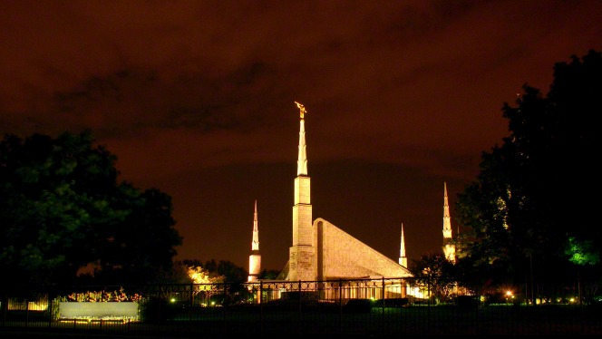 The Dallas Texas Temple lit up in the evening, set against the backdrop of a deep orange sky.