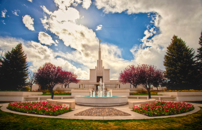 A wide-angle view of the Denver Colorado Temple on a sunny spring day, with trees and flowers in full bloom on the temple grounds.