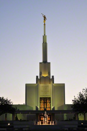The front entrance of the Denver Colorado Temple in the evening, lit up from within and without, with a water fountain in the foreground.