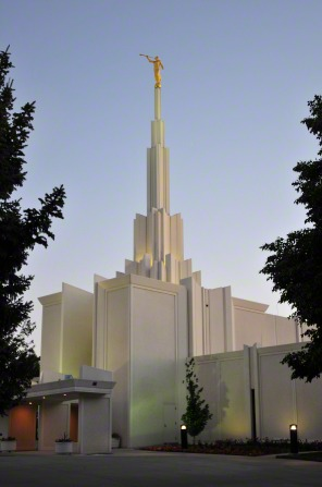 A front side view of the Denver Colorado Temple in the evening, with large trees on either side.