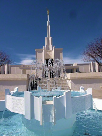 The fountain at the front entrance to the Denver Colorado Temple, with the temple seen in the background against a deep blue sky.