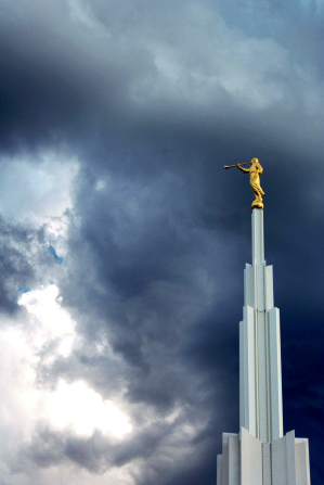 The spire and angel Moroni on top of the Denver Colorado Temple, with dark clouds in the background.