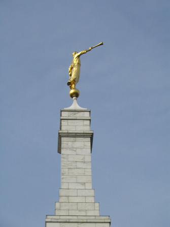 The spire and angel Moroni on top of the Detroit Michigan Temple, with a blue-gray sky in the background.