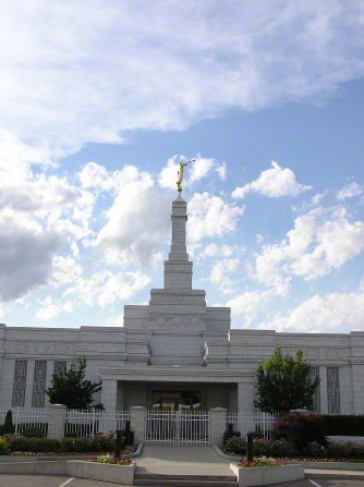 A portrait of the front entrance of the Detroit Michigan Temple, with a blue sky and white clouds in the background.
