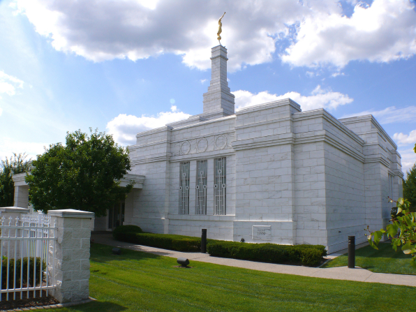 A side view of the Detroit Michigan Temple on a sunny day, with green lawns and a blue sky.