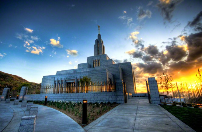 A wide-angle photograph of the Draper Utah Temple, with a bright yellow sunset on the right side.