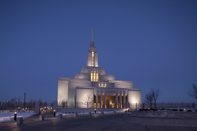 A view of the entire Draper Utah Temple at night in the winter, with yellow light coming through the windows.