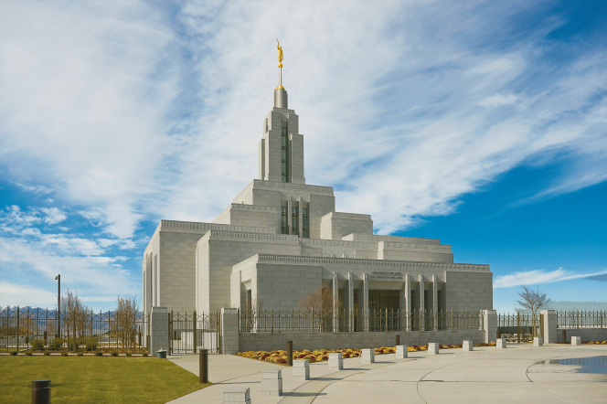 The front of the Draper Utah Temple on a sunny day, with thin white clouds overhead.