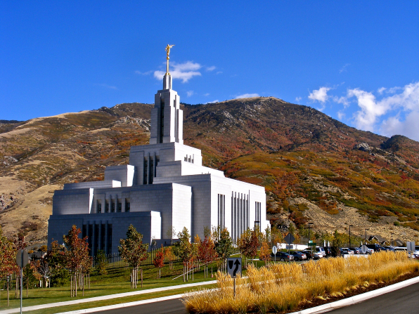 The Draper Utah Temple seen from across the street on an autumn day, with a row of trees in the temple's parking lot.