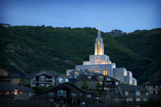 The Draper Utah Temple at night from afar, with some of the neighborhood houses seen in the front of the image and a green mountain in the background.