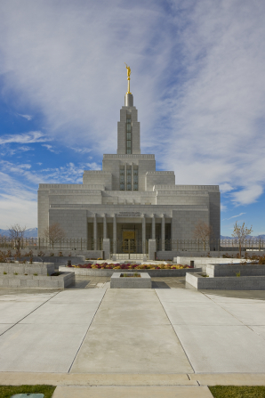 The entrance to the Draper Utah Temple on a sunny day, with white clouds overhead.