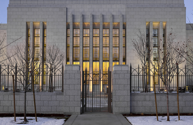 A gated fence on the grounds of the Draper Utah Temple in the evening, with the lighted windows of the temple seen beyond the fence.