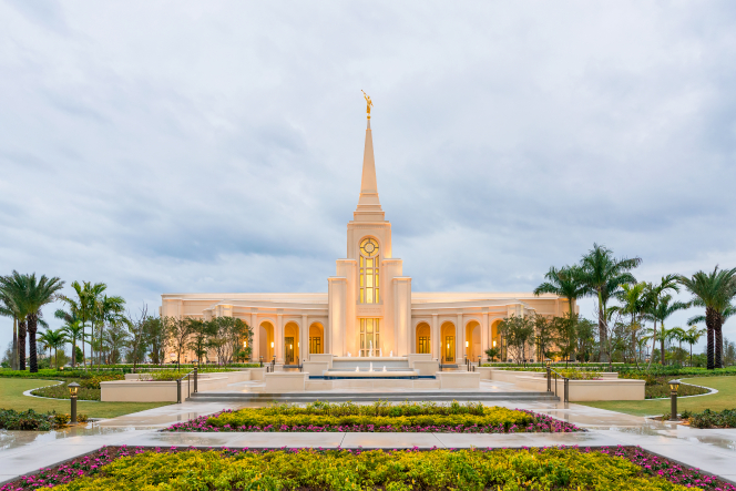 The front of the Fort Lauderdale Florida Temple in the early evening just as the lights have come on, with the fountains running near the entrance.