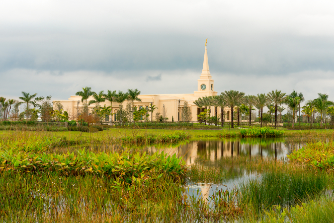 The Fort Lauderdale Florida Temple from afar, with a pool of water reflecting the temple's image amidst green grass.