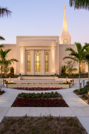 A side view of the Fort Lauderdale Florida Temple in the evening, showing a large stained-glass window with yellow light coming through.