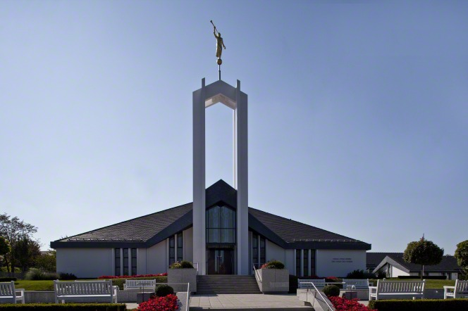 A view of the front of the Freiberg Germany Temple partially in shadow, with a clear blue sky in the background.
