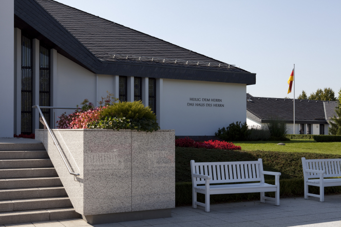 The entrance to the Freiberg Germany Temple, with large white benches in the courtyard and a German flag on the grounds.