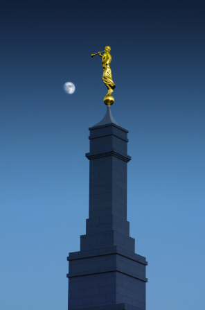 The spire of the Fresno California Temple and the angel Moroni at nighttime, with the moon on the left side.