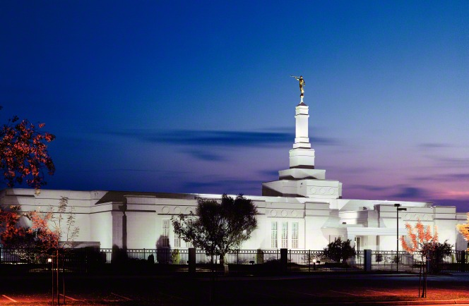 The Fresno California Temple lit up against the evening sky.