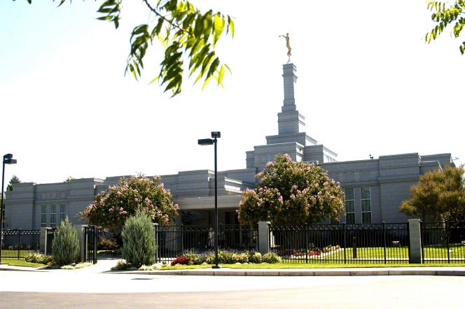 The Fresno California Temple in the daytime, with a black fence surrounding the temple grounds.