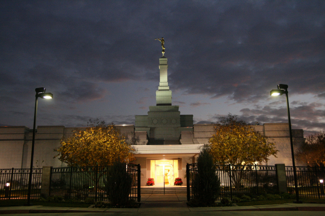 The entrance to the Fresno California Temple in the evening, with the lights illuminating the temple against the dark gray sky.