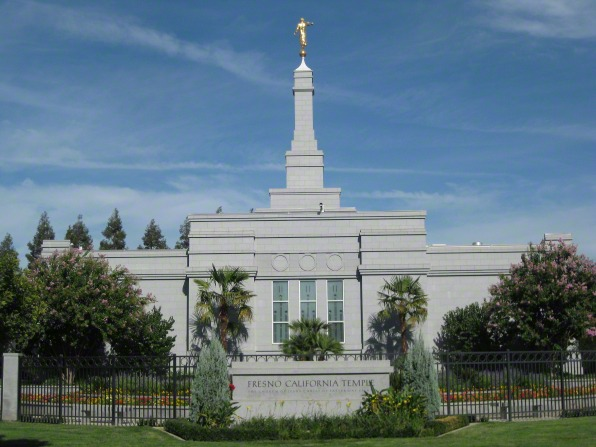 A view of the Fresno California Temple, with the temple's granite sign in the foreground and green trees on the temple grounds.