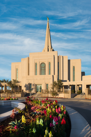 The front of the Gilbert Arizona Temple, with a flower bed in full bloom curving to the right.