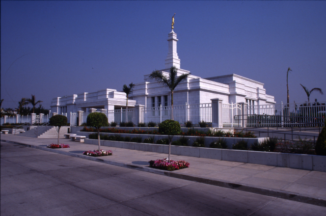 A photo of the Guadalajara Mexico Temple, taken from the parking lot, with a clear blue sky in the distance.